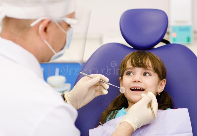 Stomatologicznym egzamininuje dawać mała dziewczynka dentystą obraz stock