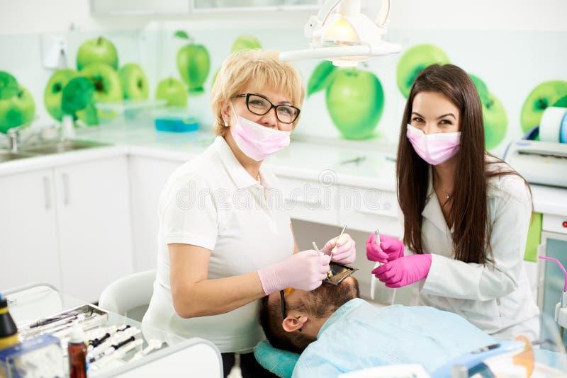 Stomatologist и ассистент во время обработки пациента усмехнулись в камеру стоковая фотография rf