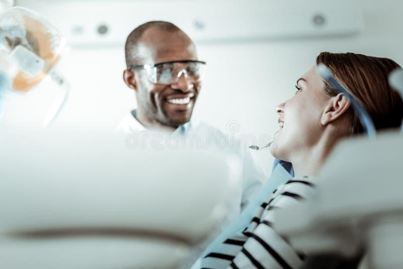 Stomatologist с белыми зубами кладя его инструменты в рот стоковая фотография rf
