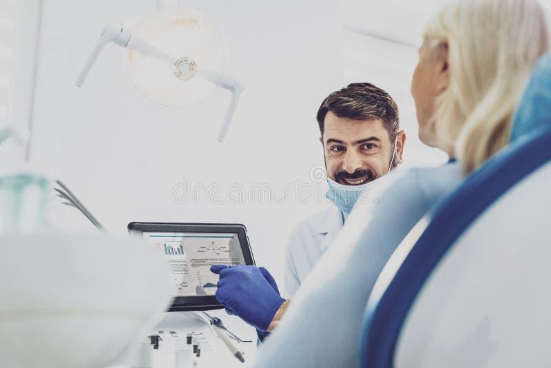 Stomatologist alegre que comunica con su visitante fotos de archivo