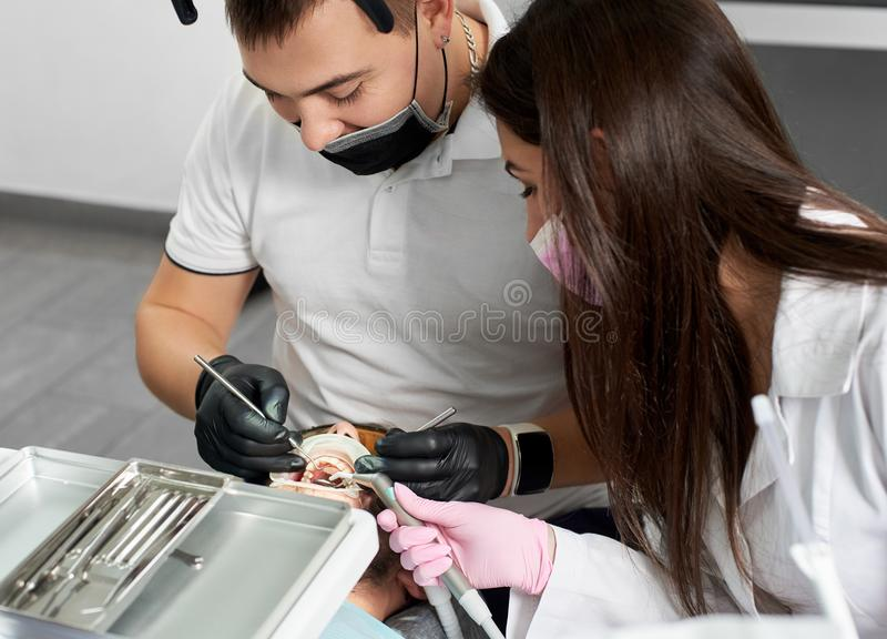 Stomatologist and assistant working on a male patient in clinic royalty free stock images