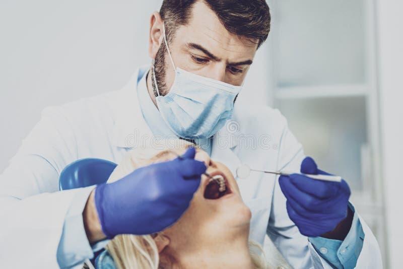 Stomatologist attentif examinant son patient photos libres de droits