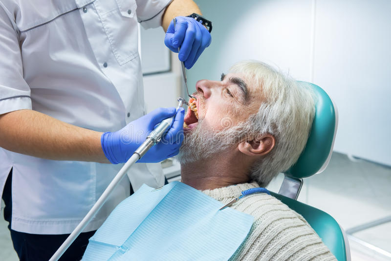 Stomatologist is cleaning teeth. Senior male at the dentist. Importance of hygiene for health royalty free stock image