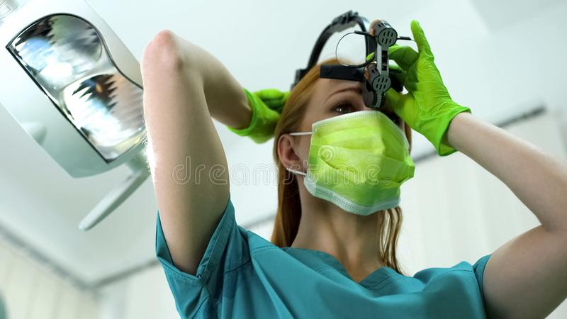 Stomatologist da senhora que põe lupa sobre, equipamento dental da clínica foto de stock