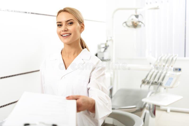 Stomatologist, das ihrem Kunden im Büro freien Raum gibt stockbild