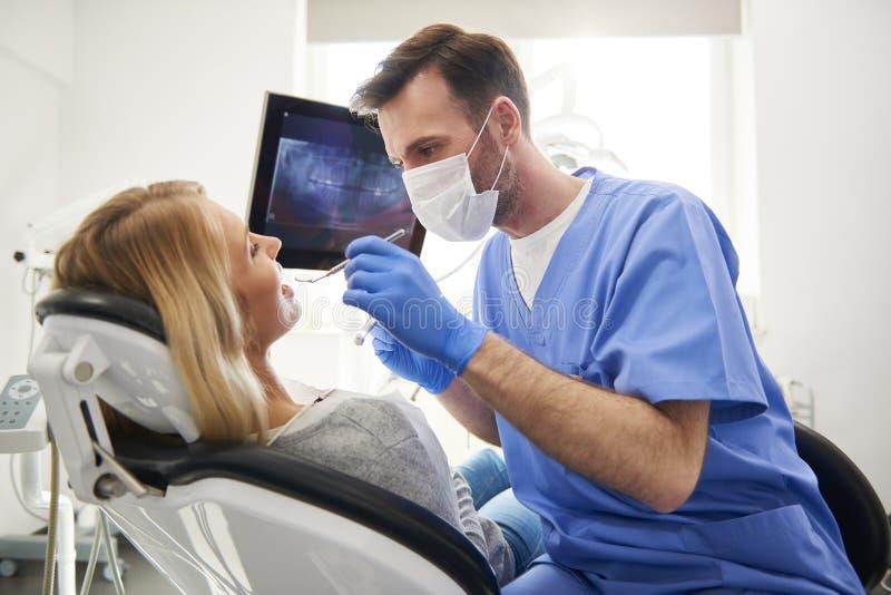 Stomatologist effectuant son travail dans la clinique du dentiste photo stock