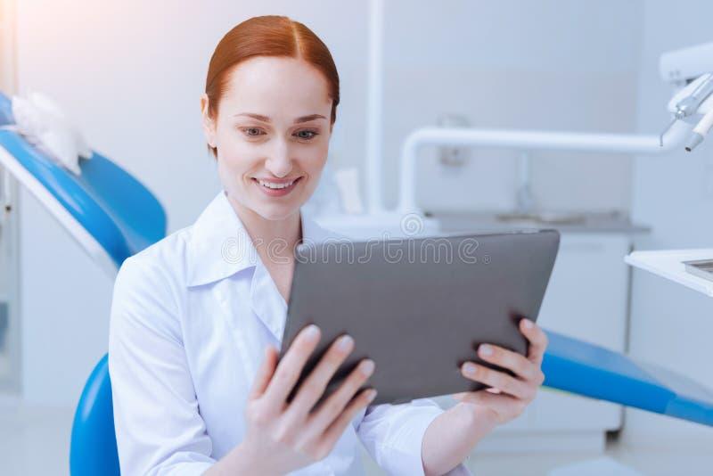 Stomatologist encantado positivo que se sienta en su gabinete fotografía de archivo