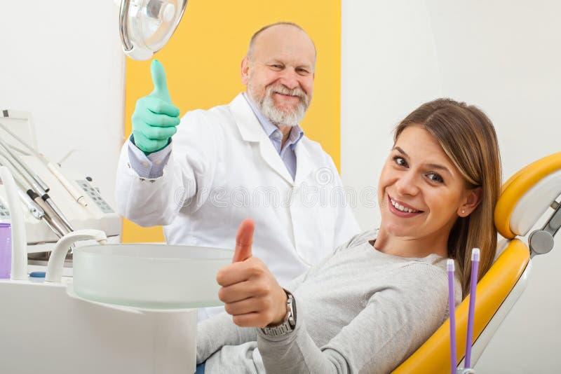 Stomatologist et patient féminin montrant des pouces  photographie stock