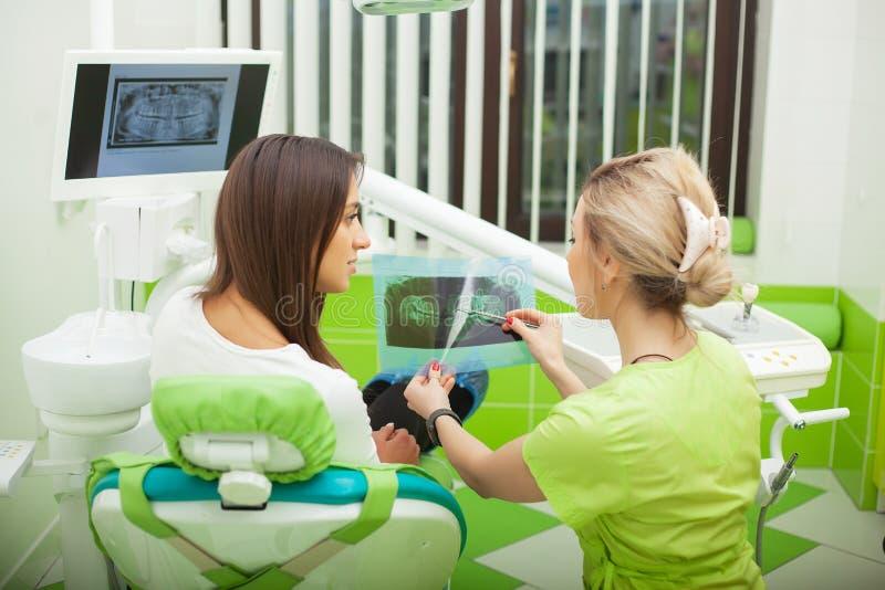 Stomatologist femenino en los guantes protectores que examinan los dientes del paciente Tratamiento de la carie del dentista en l fotos de archivo libres de regalías