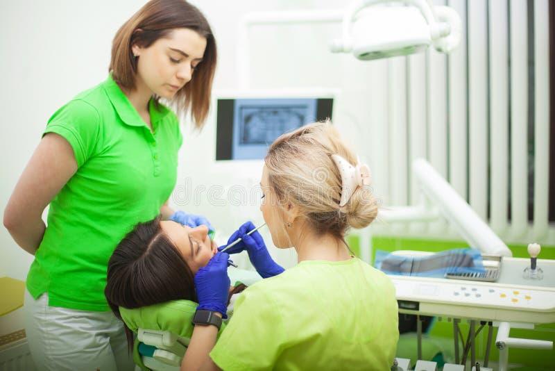 Stomatologist femenino en los guantes protectores que examinan los dientes del paciente Tratamiento de la carie del dentista en l imágenes de archivo libres de regalías