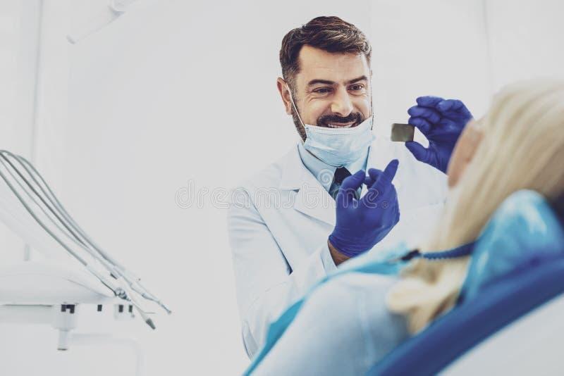 Stomatologist heureux se dirigeant à la photo de rayon X photo stock