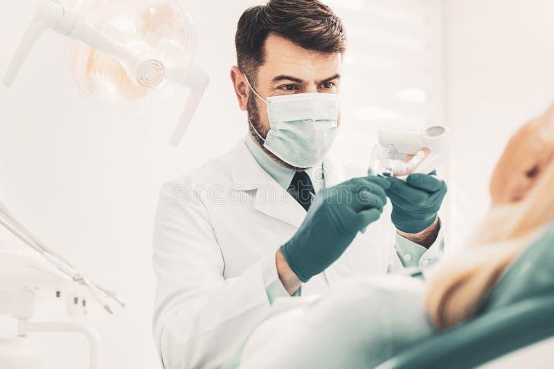 Stomatologist montrant la maquette dentaire photographie stock libre de droits