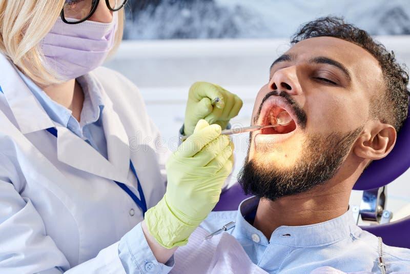 Stomatologist profesional envuelto para arriba en trabajo imagen de archivo