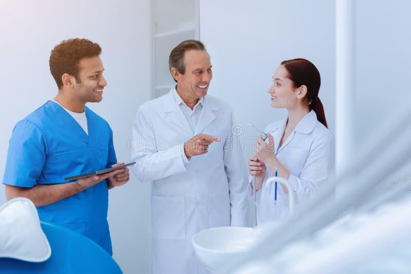 Stomatologist profesional que habla con sus ayudantes imagen de archivo libre de regalías