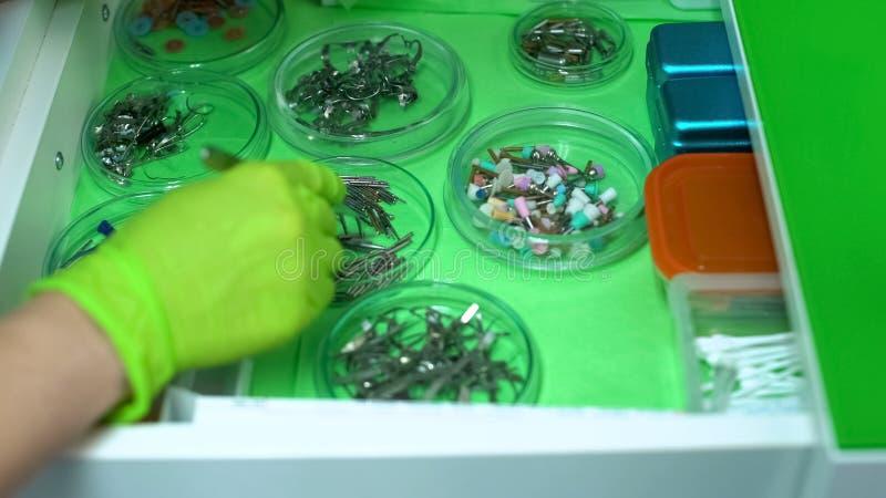 Stomatologist que elige los instrumentos para curar los dientes de los pacientes, ayuda profesional fotos de archivo