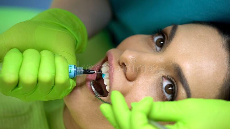 Stomatologist som applicerar blått, stelnar på tanden, kosmetisk tandläkekonst, estetik fotografering för bildbyråer