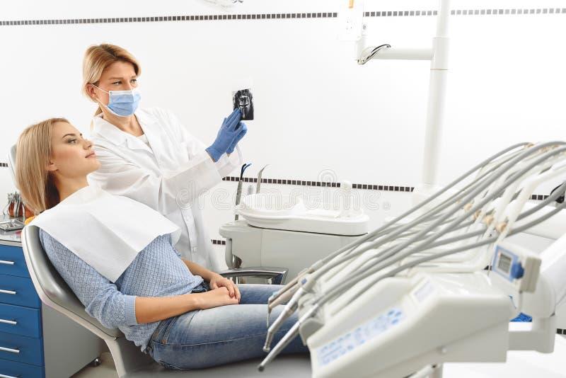 Stomatologist som pekar uppsättningen av hål i röntgenbild royaltyfri foto