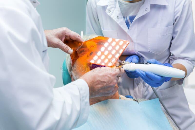 Stomatologist usando la luz ultravioleta foto de archivo libre de regalías