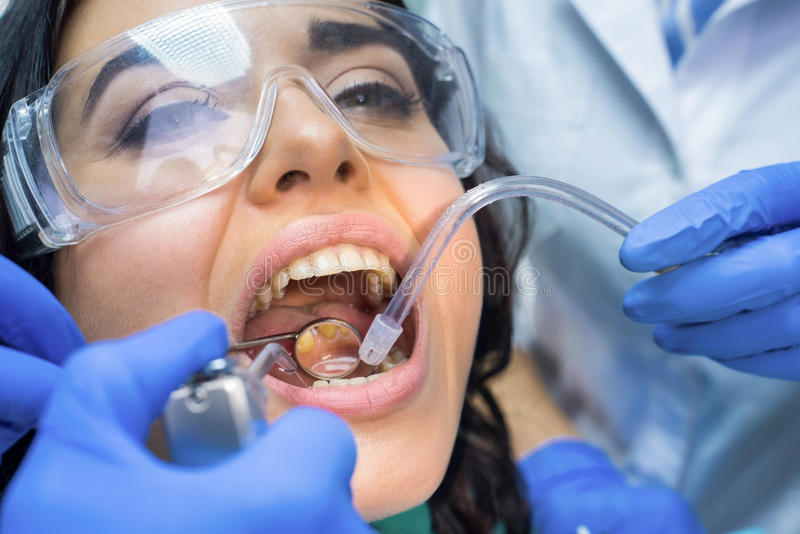 Stomatologist using concave mirror. Female patient with open mouth stock photo