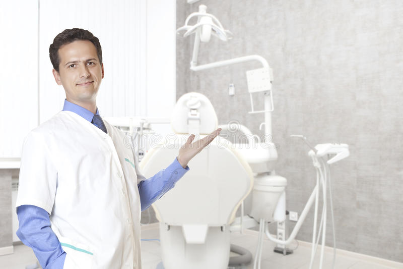 Stomatology concept - happy male dentist at dental clinic office. People, medicine, stomatology and healthcare concept - happy male dentist in white coat at stock photo