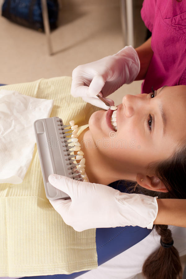 Stomatology is fun: choose the right color. Dentist is choosing the right color for dental filling stock images