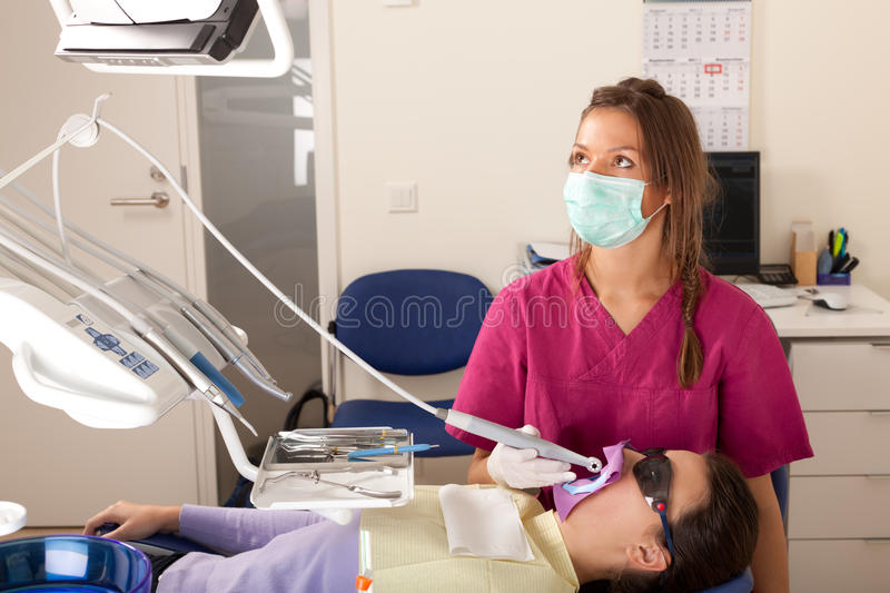 Stomatology is fun: video mode. Dentist is examining patient's teeth using camera stock images