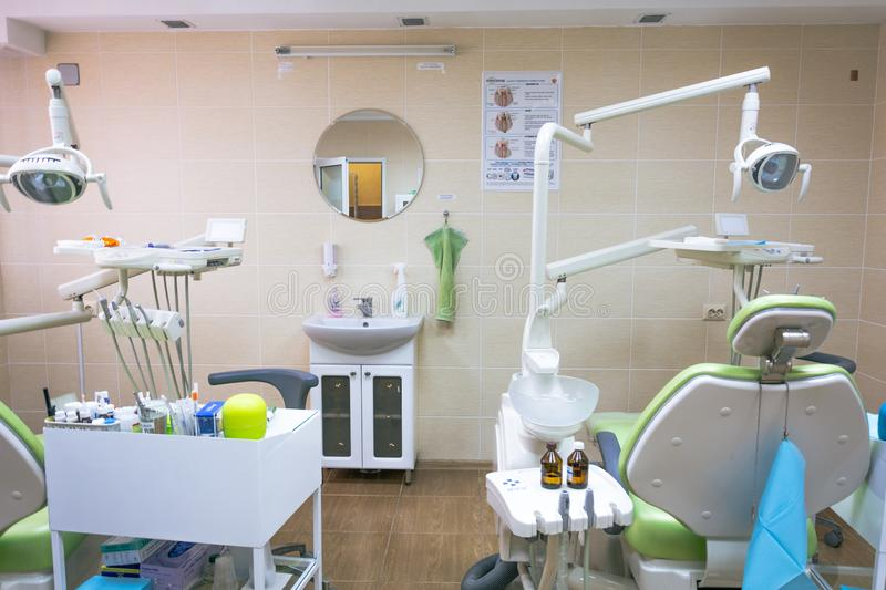 Stomatology interior of small dental clinic with professional chair in green colors. Dentistry, medicine, medical equipment and stock images