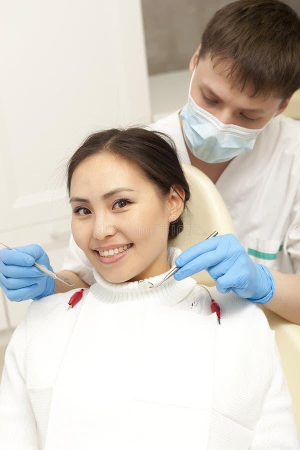 Stomatologybegrepp - manlig tandläkare med spegeln som kontrollerar patienten royaltyfri foto