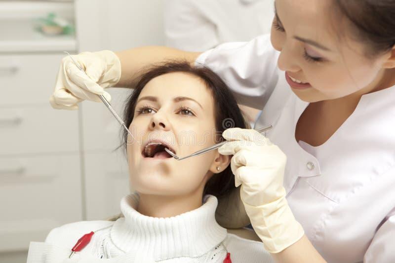 Stomatologybegrepp - tandläkare med spegeln som kontrollerar den tålmodiga flickan arkivbilder
