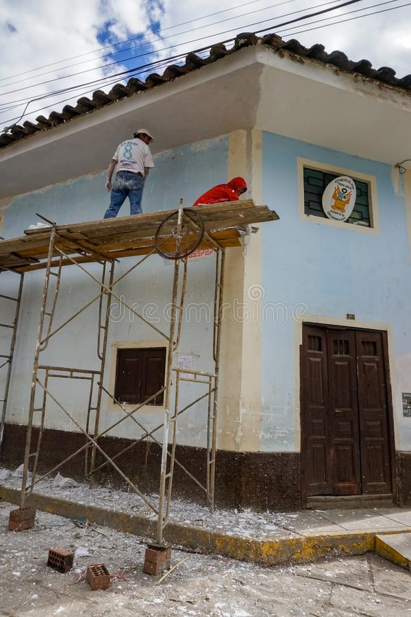Stomemason et travailleurs de peintre sur un échafaudage rénover une maison dans un village à distance au Pérou image libre de droits