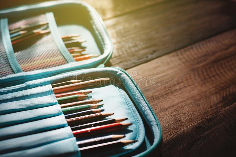 Stomp gekleurd potlood in een potloodgeval op af een houten bureau in een somber licht royalty-vrije stock foto's