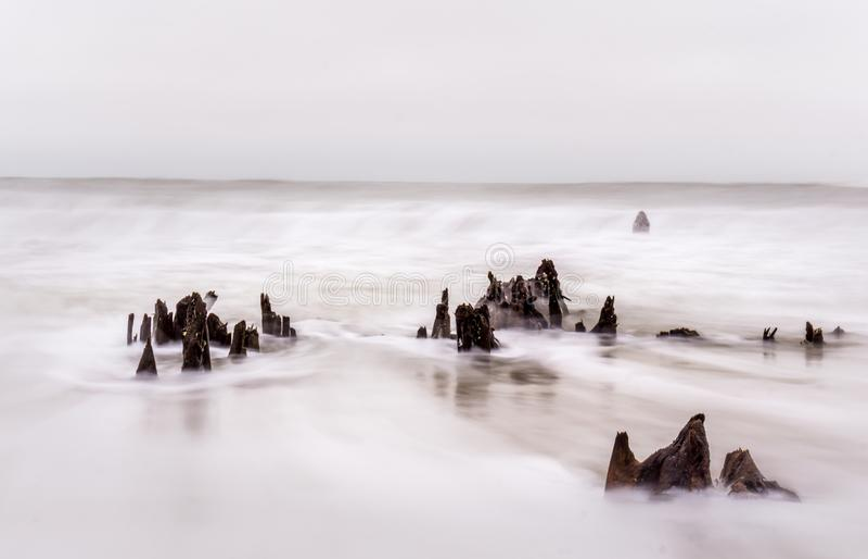 Stompen in stromende oceaanbranding stock afbeeldingen