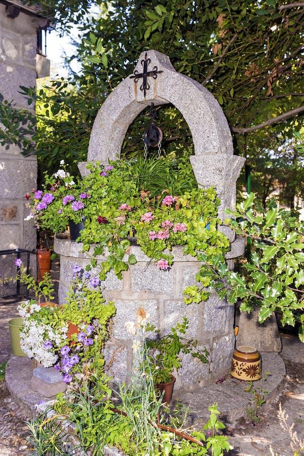 Stone καλά το νερό που διακοσμείται για με τα λουλούδια στοκ φωτογραφίες