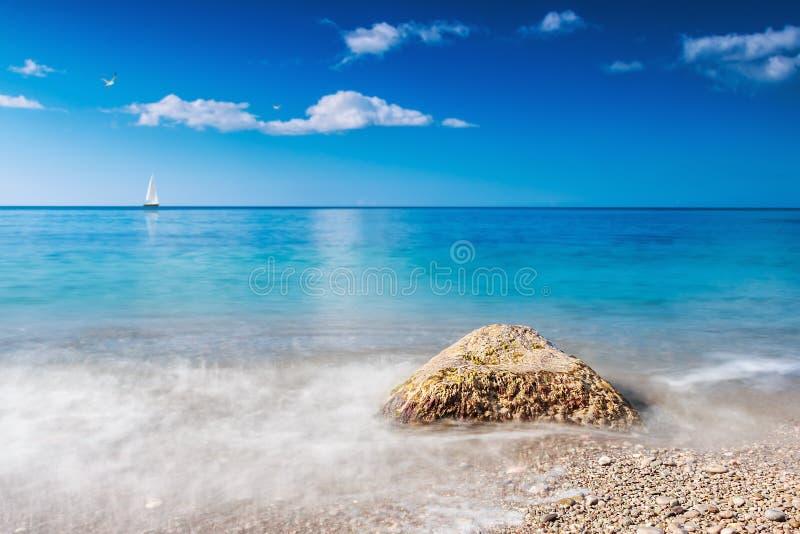 Stone που πλένεται από τα κύματα και τα πανιά βαρκών στοκ εικόνα με δικαίωμα ελεύθερης χρήσης