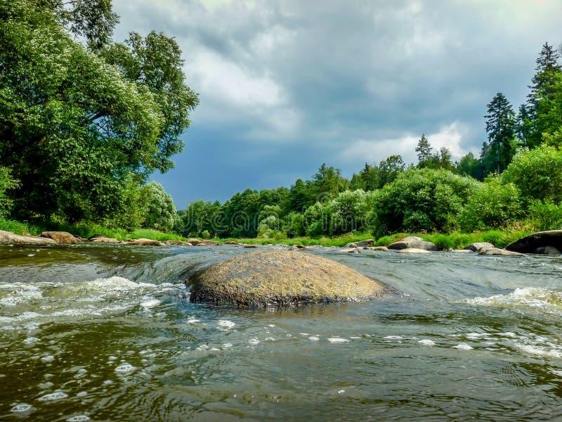 Stone στον ποταμό με έναν σκοτεινούς ουρανό και ένα δάσος στοκ εικόνες