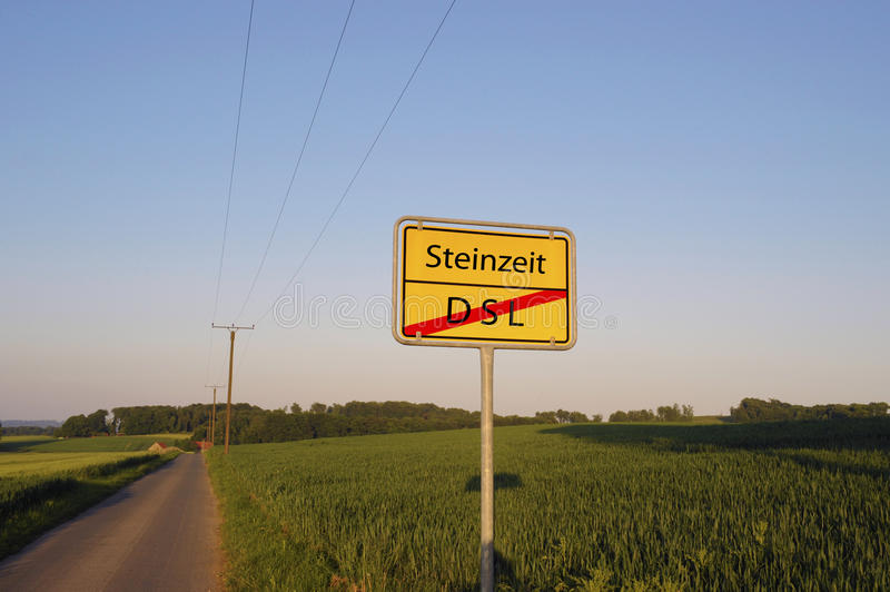 Stone age no DSL sign. Sign reading Steinzeit with a red line through DSL beneath it (translation: Stone age, no DSL), posted beside a road in a rural German royalty free stock images