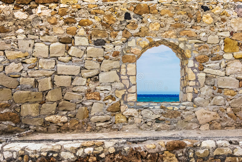 Stone ancient wall with a window. Sea view stock images