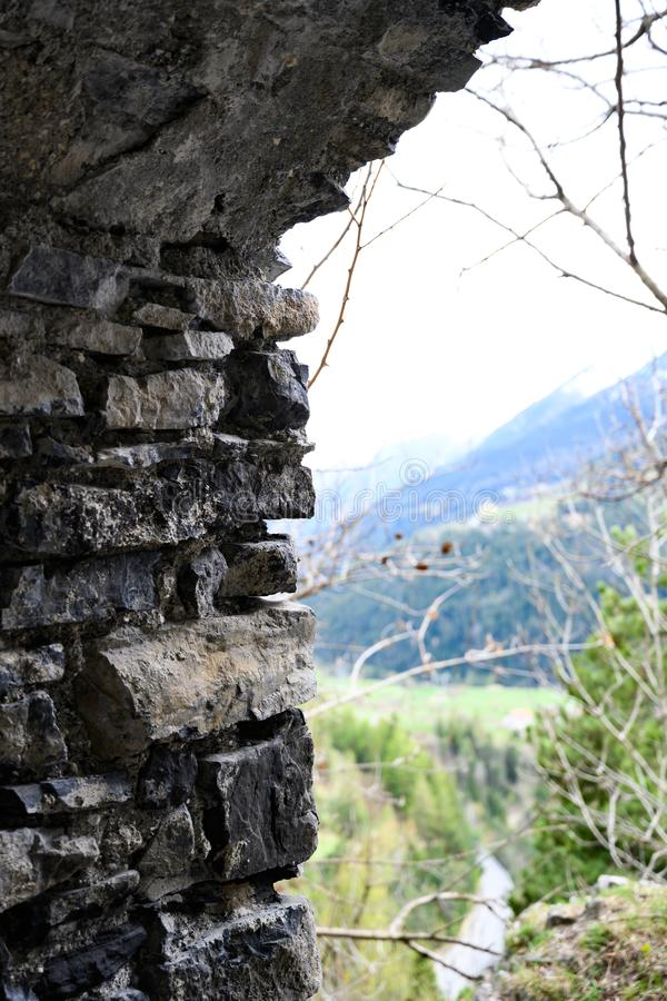 Stone arch looking over a valley. Stone arch in the Italian Alps overlooking a green valley in spring stock photos
