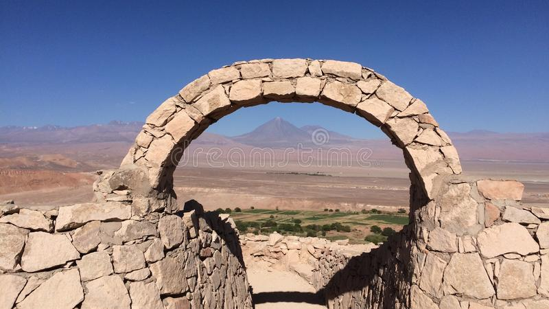 Stone arch with volcano, atacama desert, chile royalty free stock photo