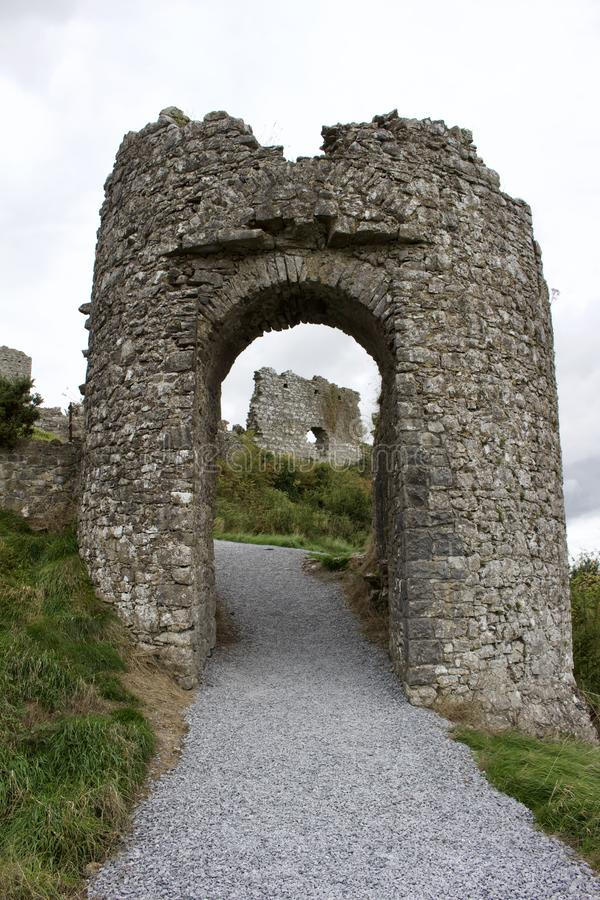 Stone archway to Medieval castle ruins in rural Ireland on an overcast day. Stone archway on a walkway up to a Medieval stone castle ruins in rural Ireland Rock royalty free stock photography