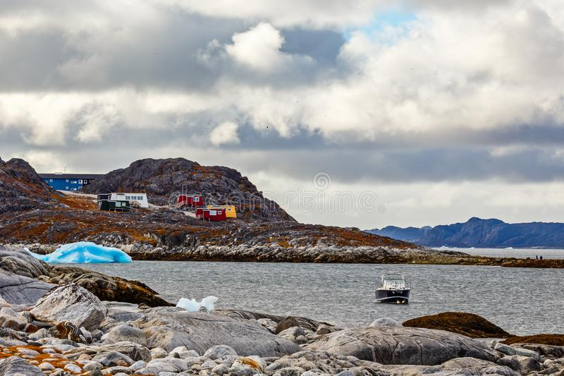 Stone arctic coast, motorboat and blue iceberg floating in the b. Ay with small colorful houses on the rocks in background, Nuuk, Greenland royalty free stock photography