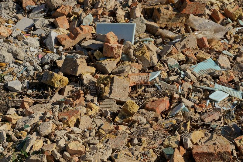 Stone texture from garbage pieces of brown bricks and tiles in a pile on the ground. Stone background of garbage pieces of brown bricks and tiles in a pile on royalty free stock photography