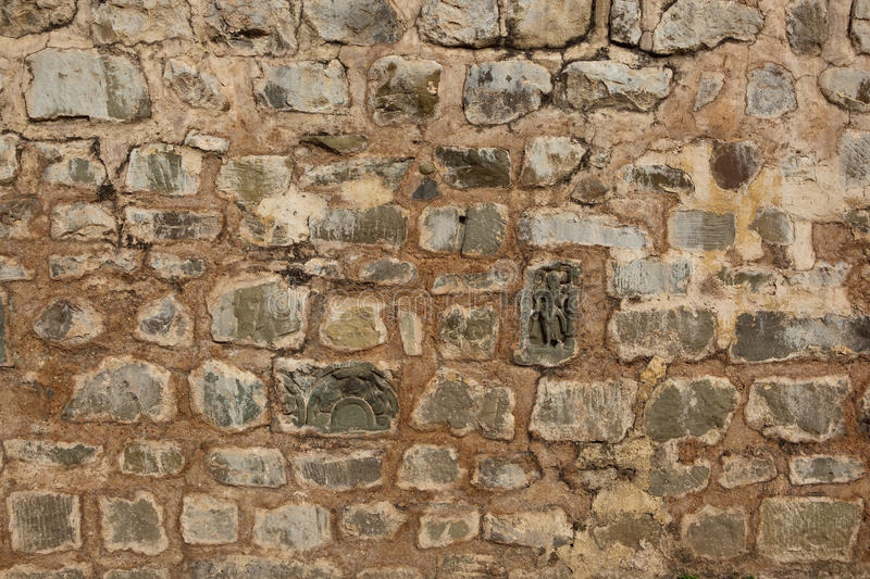 Stone background. Patterns and textures of a wall of reclaimed stone including ancient carved pieces royalty free stock image