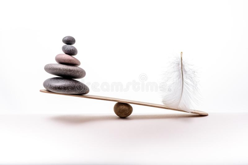 Stone balance with plume. Concept of heavy and light. Meditation stones and plume isolated on white background stock image