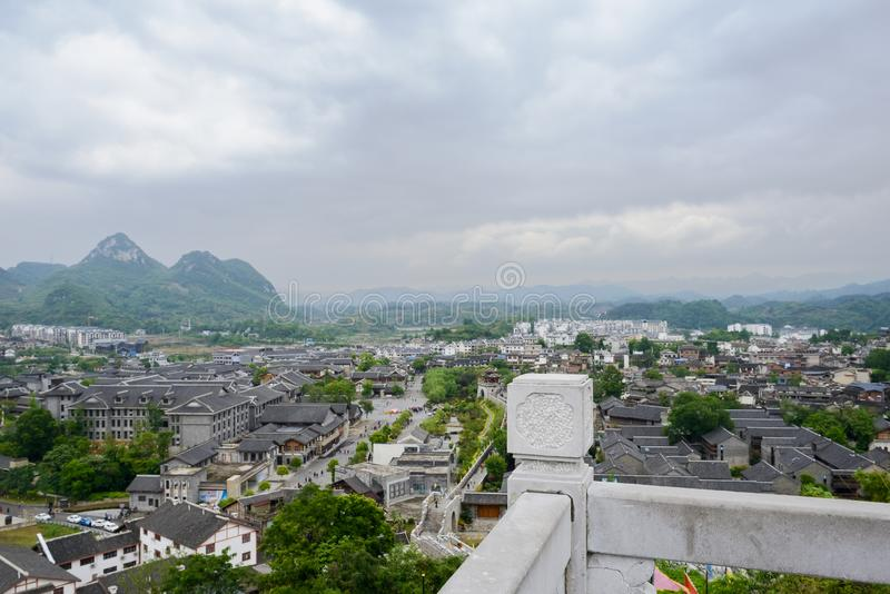 Stone balustrade of hilltop platform overlooking ancient town in. Mountains on cloudy spring day,Qingyan town,Guiyang,China stock photos