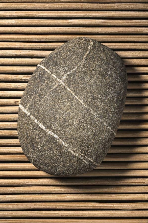 Stone on bamboo. Single Stone on bamboo background stock photo