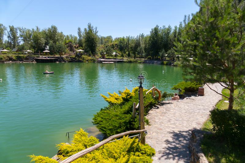 Stone banks of a large lake with planted decorative bushes for recreation of tourists. For your design stock photography