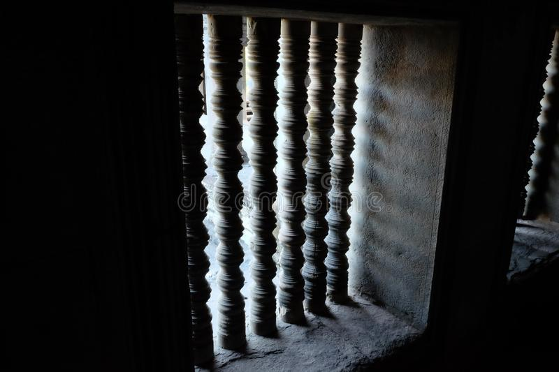 Stone bars on the windows. The window opening of the old house. Light and shadow stock image