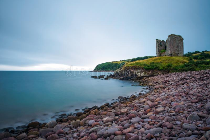 Stone beach and the Minard Castle situated on the Dingle Peninsula in Ireland. Beautiful stone beach and the Minard Castle situated on the Dingle Peninsula with stock photography