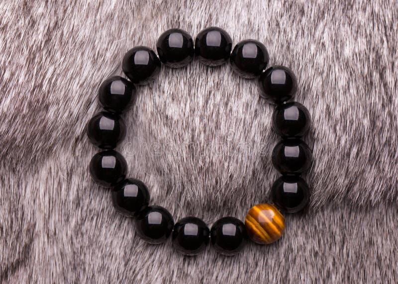 Stone bead bracelets handmade from lucky stones. Bracelet from dark beads royalty free stock photo